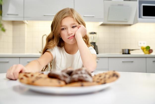 Menina triste olhando biscoitos americanos, sentado na cozinha.
