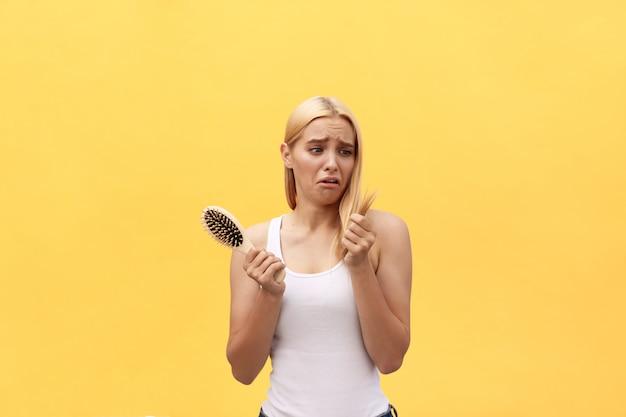 Menina triste olhando para o cabelo danificado com pente na mão