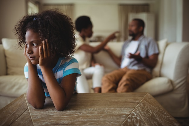 Menina triste, ouvindo seus pais discutindo