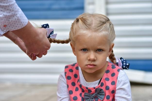 Menina triste se senta e espera enquanto a mãe trança o cabelo do cabelo dela