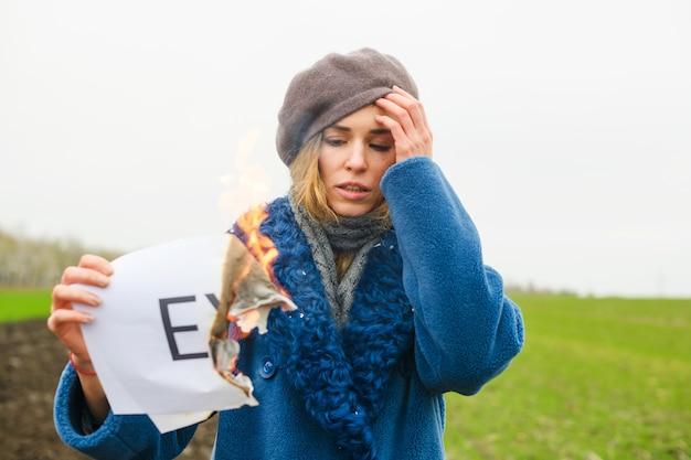 Menina triste segura papel queimando com fogo e imprime a palavra ex sobre namorado, marido, relacionamento rompido, ritual de divórcio
