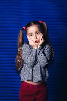 Menina triste segurando a bochecha sobre uma superfície azul. conceito de dor de dente infantil.
