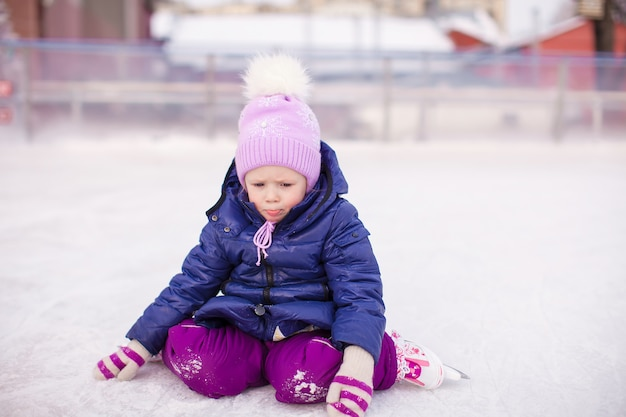 Menina triste sentada no gelo com patins após a queda