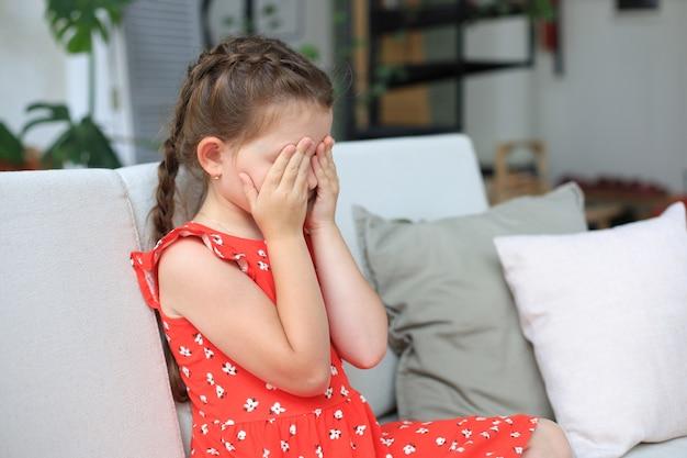 Menina triste sentada no sofá sozinha em casa. Foto Premium