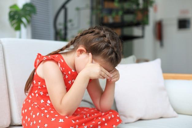 Menina triste sentada no sofá sozinha em casa.