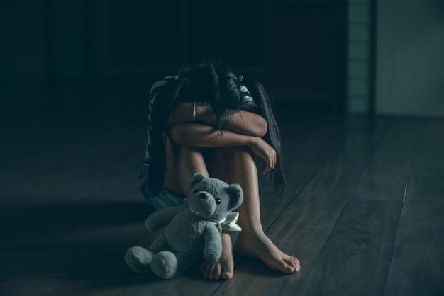 Menina triste sentada sozinha com o ursinho de pelúcia no chão