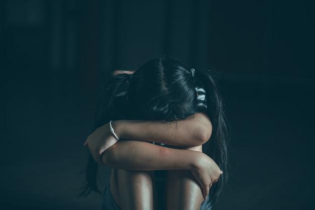 Menina triste sentada sozinha no chão