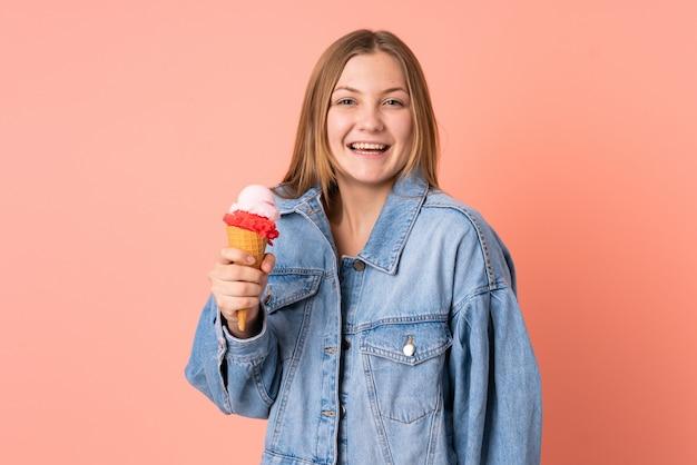 Menina ucraniana do adolescente com um sorvete de corneta isolado no rosa com surpresa e expressão facial chocada