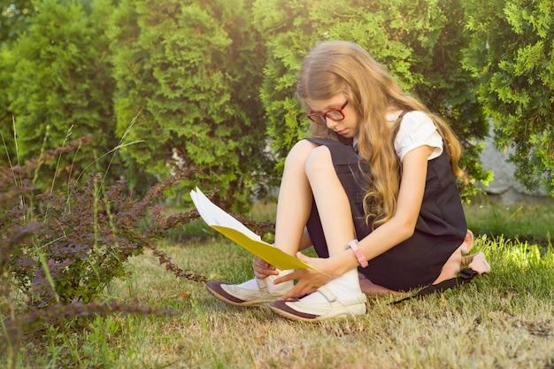Menina um aluno da escola primária, lendo o caderno da escola