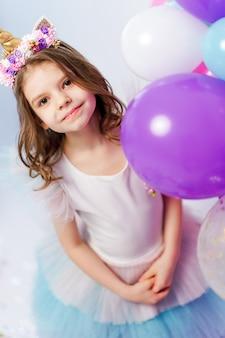 Menina unicórnio posando perto de balões de ar na festa de aniversário