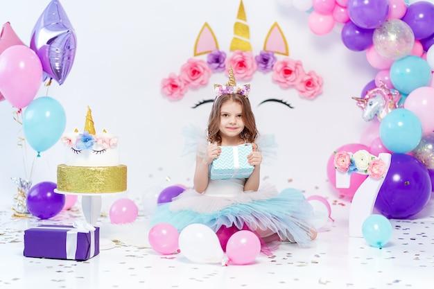 Menina unicórnio segurando a caixa de presente na festa de aniversário