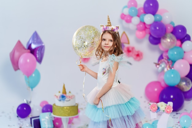 Menina unicórnio segurando balão de confete ouro na festa de aniversário
