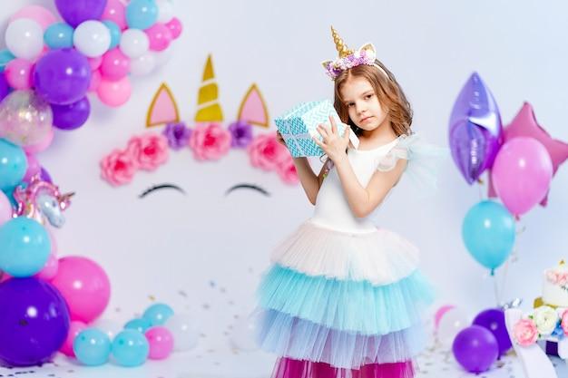Menina unicórnio segurando uma ideia de caixa de presente para decorar o estilo unicórnio