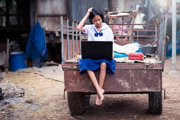 Menina uniforme asiática do estudante que usa o caderno do computador com problema e dor de cabeça.