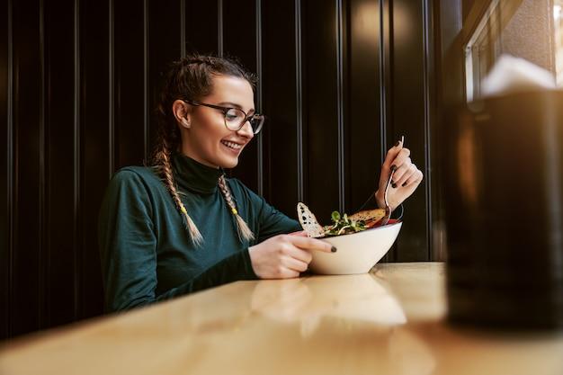 Menina universitária sorridente sentada no restaurante, comendo salada no almoço na pausa.