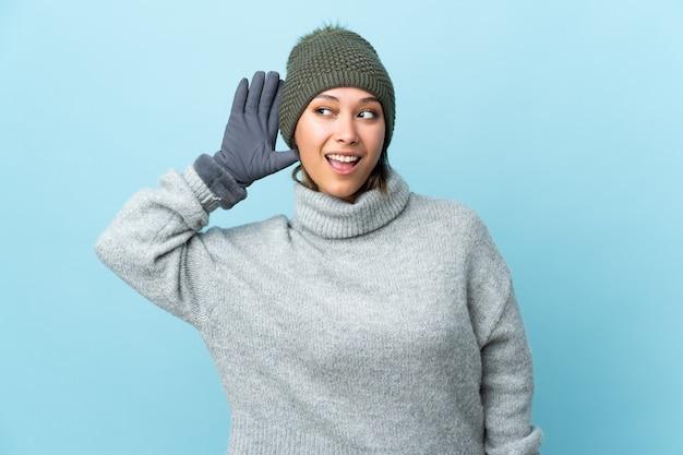 Menina uruguaia nova com o chapéu do inverno isolado no azul que escuta algo