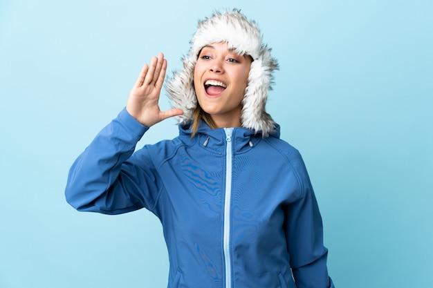 Menina uruguaia nova com o chapéu do inverno isolado no azul que shouting com a boca aberta