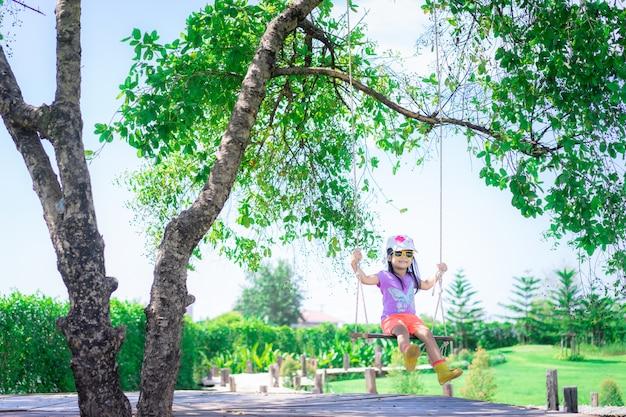 Menina usa chapéu e óculos de sol sentado em um balanço no parque