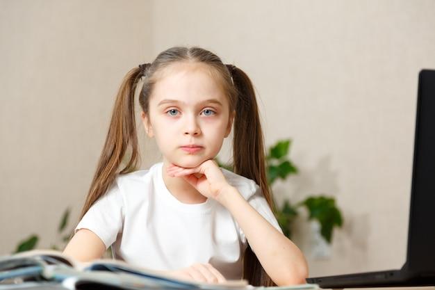 Menina usa laptop para aprender em casa.