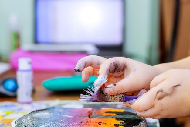 Menina usa tintas coloridas pincéis uma imagem em madeira