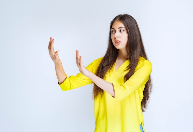 Menina usando as mãos para parar algo enquanto está apavorada.
