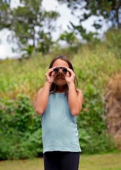Menina usando binóculos em uma caça ao tesouro