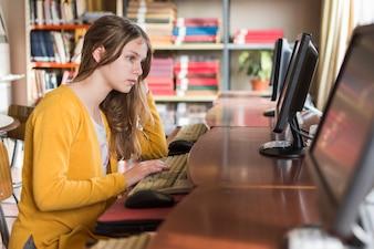 Menina, usando computador, em, biblioteca