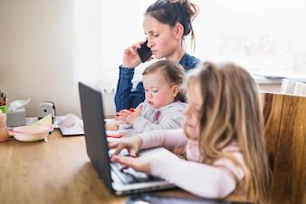 Menina, usando computador portátil, ao lado, dela, mãe fala, ligado, smartphone