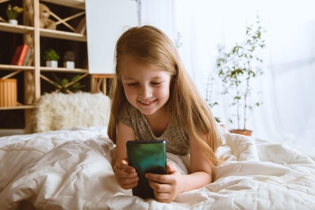 Menina usando diferentes aparelhos em casa