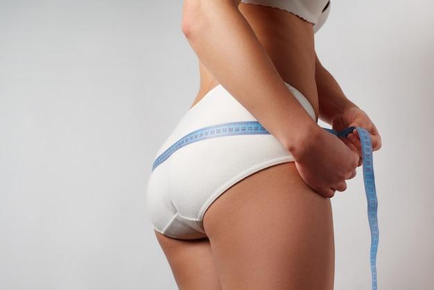 Menina usando fita métrica mede a circunferência das nádegas