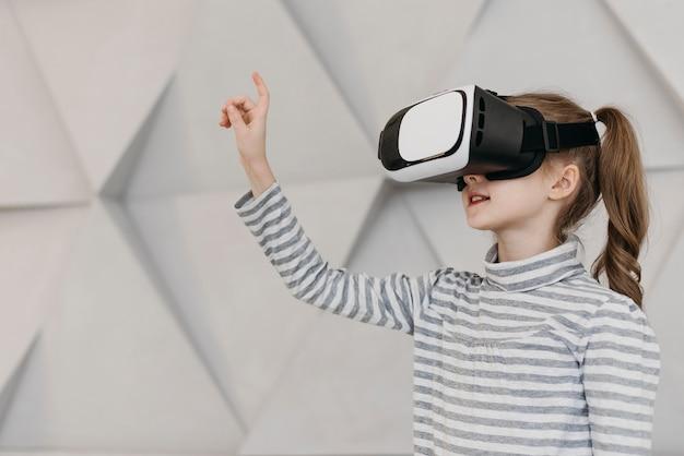 Menina usando fone de ouvido de realidade virtual e segurando a mão no ar