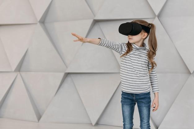 Menina usando fone de ouvido de realidade virtual esticando a mão