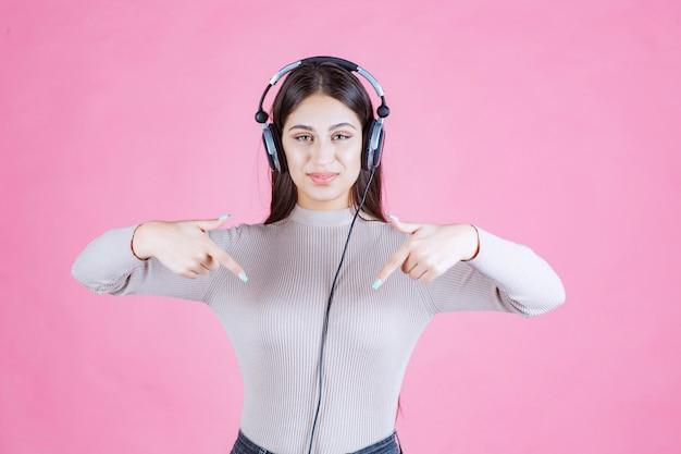 Menina usando fones de ouvido e apontando para algum lugar