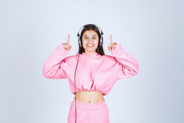 Menina usando fones de ouvido e apontando para cima. foto de alta qualidade