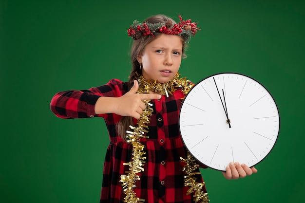 Menina usando guirlanda de natal em um vestido xadrez com enfeites em volta do pescoço segurando um relógio de parede apontando com o dedo indicador para ele, parecendo confusa em pé sobre a parede verde