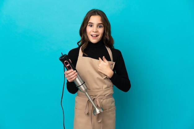 Menina usando liquidificador isolado na parede azul com expressão facial surpresa
