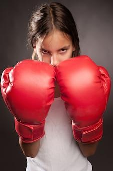 Menina usando luvas de boxe vermelhas