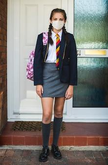 Menina usando máscara e indo para a escola no novo normal
