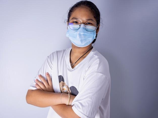 Menina usando máscara e óculos em pé com os braços cruzados sobre um fundo branco