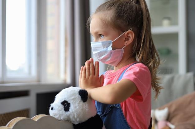 Menina usando máscara para proteger covid-19. ela está orando pela manhã por um novo dia de liberdade para o vírus corona mundial. mão da menina rezando para agradecer a deus.
