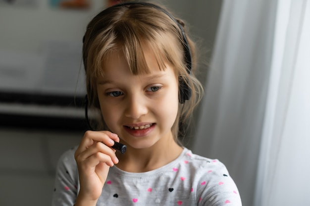 Menina usando o bate-papo por vídeo no laptop em casa. espaço para texto