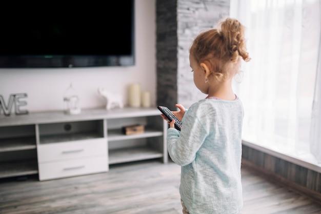 Menina usando o controle remoto da tv