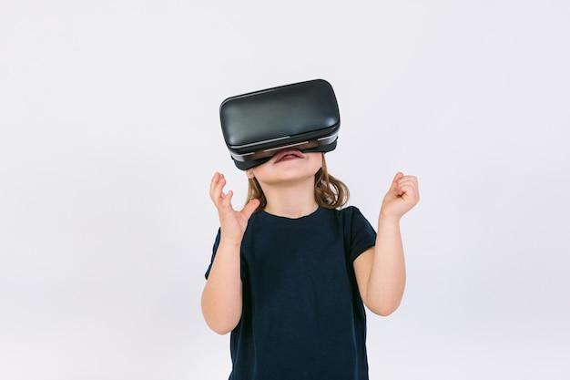 Menina usando óculos de realidade virtual com as mãos tentando tocar algo virtualmente, em fundo branco