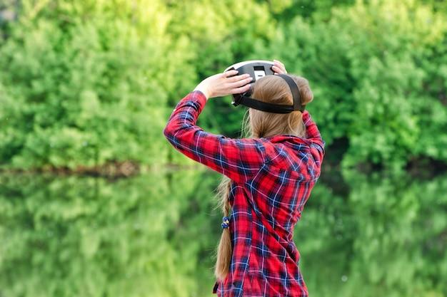 Menina usando óculos de realidade virtual na natureza