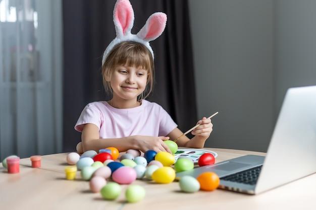 Menina usando orelhas de coelho e pintando ovos de páscoa em casa.