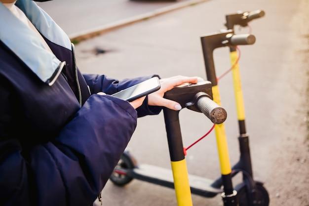 Menina usando seu aplicativo de celular para uma e-scooter de aluguel.