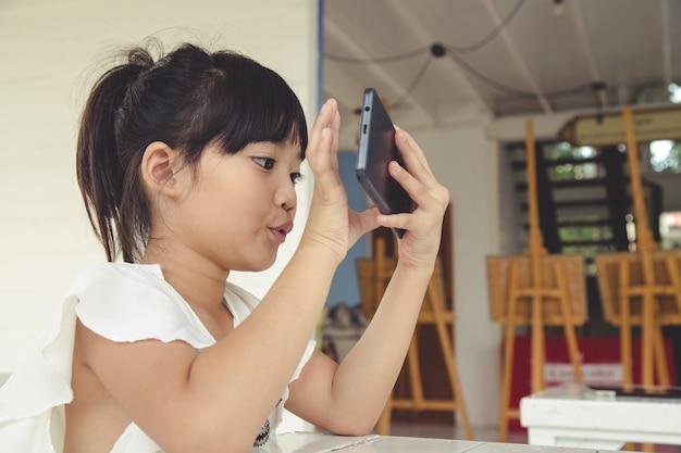 Menina usando smartphone, conceito de mídia social.