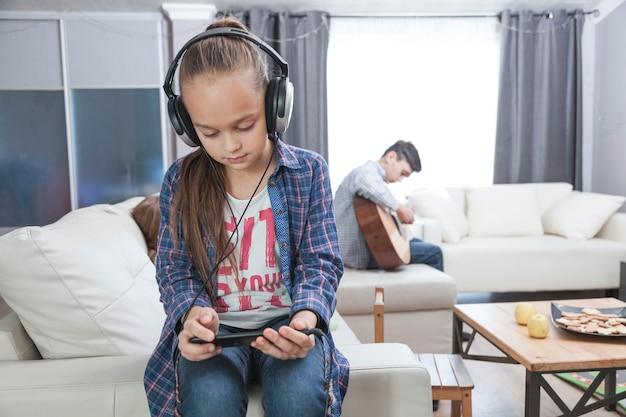 Menina, usando, smartphone, em, sala de estar