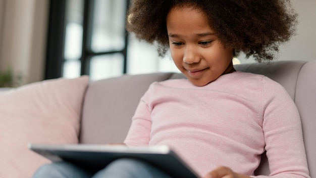 Menina usando tablet em casa