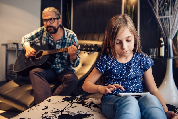 Menina usando tablet na sala de estar